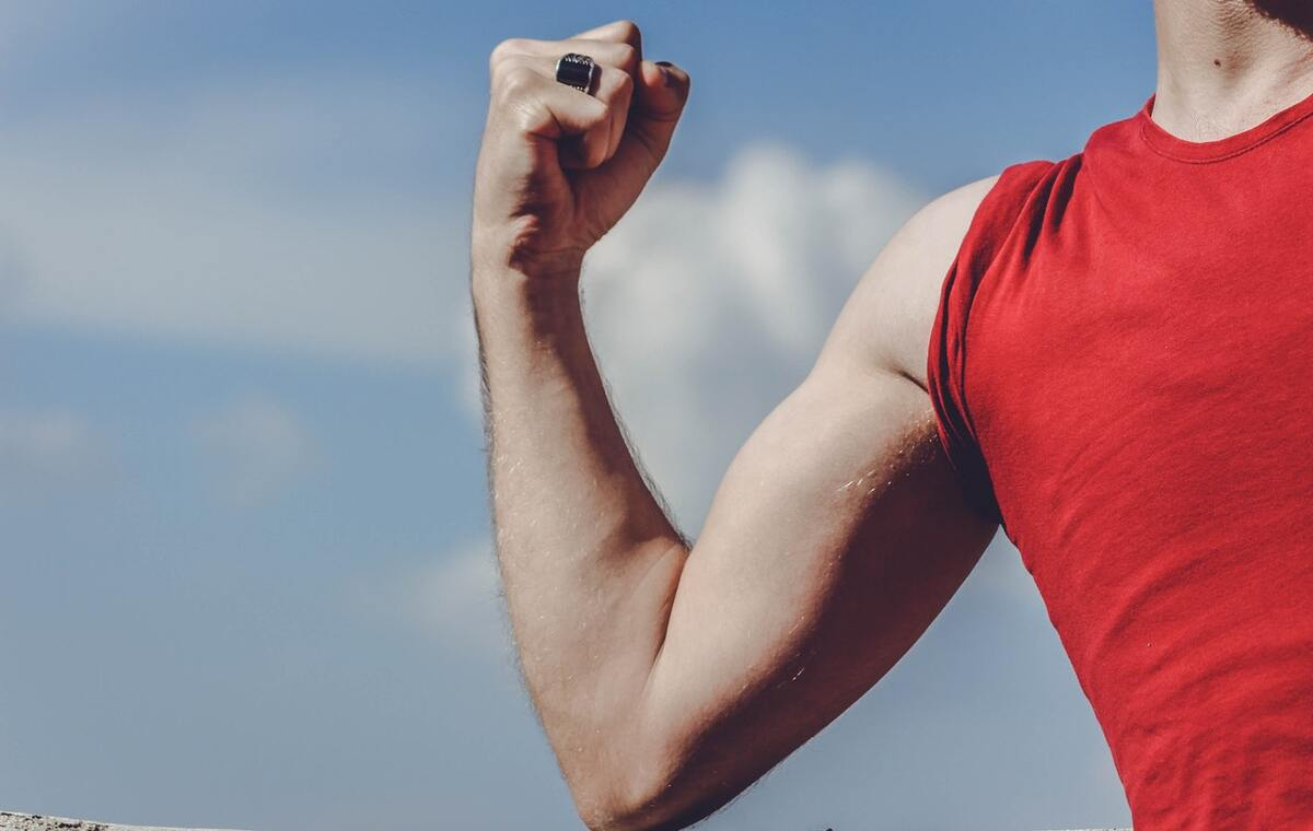 man showing his biseps in red tshirt