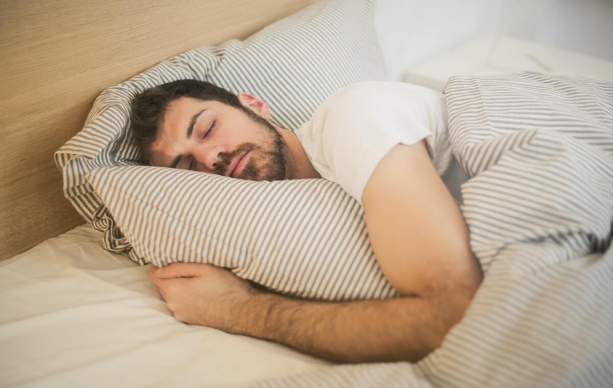 photo of a man sleeing in a bed
